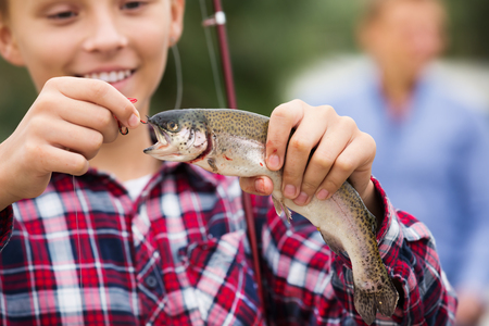 Glad teenager boy holding and looking at the fish on a hook 写真素材