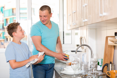 Boy and his father are helling mother and washing dishes at the home.