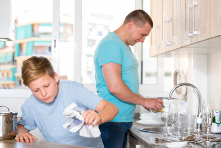 Smiling bou is washing dishes with his father together at the home.