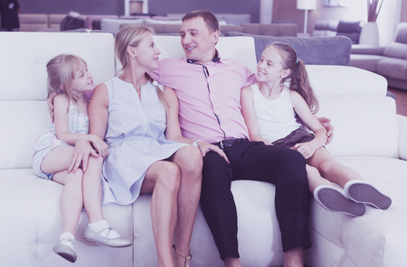 Happy family selecting new sofa in modern furniture store
