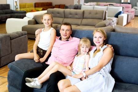 Positive young family is satisfied by new bought sofa in the store