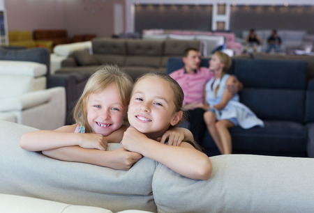 Little sisters which are happy of the purchase of a new sofa in the store.