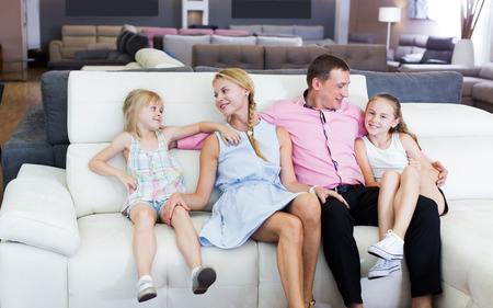 Man and woman with kids is pleased by new sofa in furniture store Stock fotó