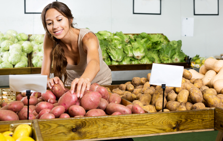 Portrait of young positive woman buying potatoes in food store