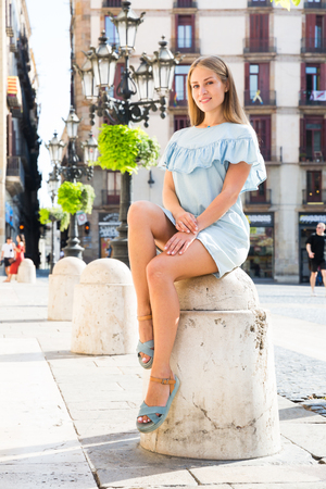 Attractive smiling girl in lightweight blue dress sitting on stone bollard in historical center of Barcelona Stock Photo