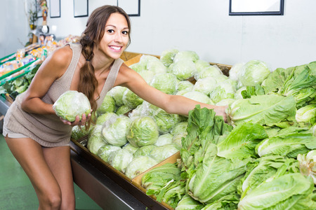 joyful young woman customer buying fresh green iceberg salad in store