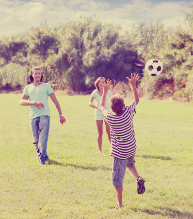 teenage boy and happy parents playing in soccer at summer park