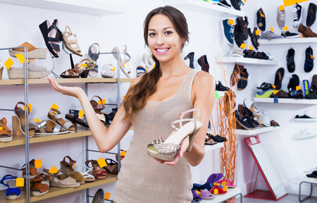 Happy woman holding desired shoe in hands in fashion boutique