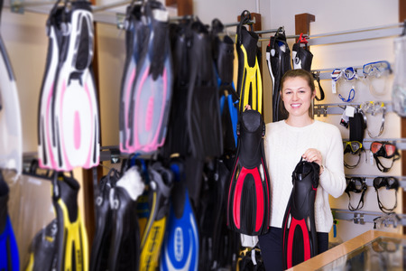 happy young female is standing with flippers for diving in the store. Stockfoto