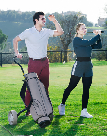 A young man watching a game girl golfer on a golf course