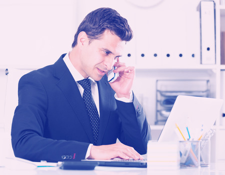 Successful businessman using phone and laptop at workplace