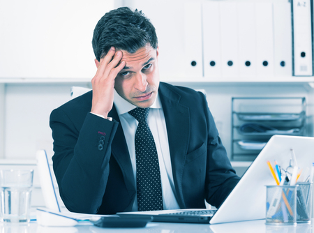 Portrait of worried manager working on laptop in office Stockfoto