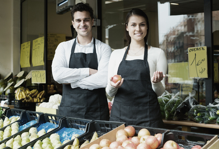 Happy sellers offering good price for vegetables and fruits Stock Photo