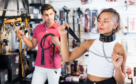 Woman and man purchasers looking black collar and leather lash in the sex shop Stockfoto - 111910225