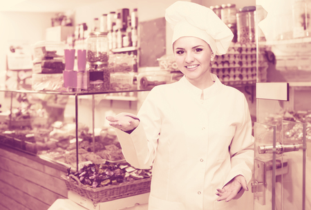 Portrait of smiling women at confectionery shop with pastry