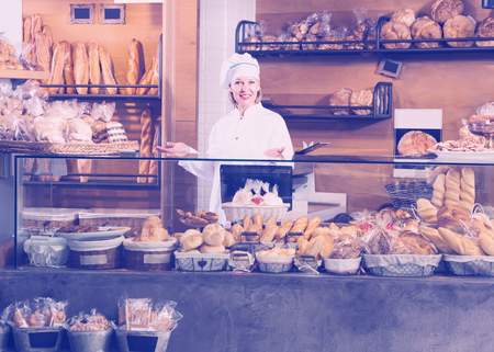 Smiling mature bakery employee offering bread and different pastry for sale Reklamní fotografie