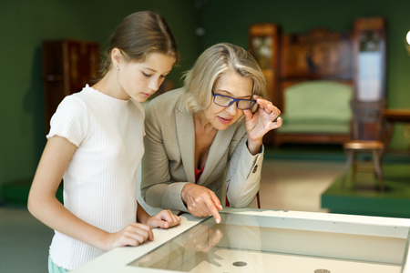 Attentive tween girl with senior woman looking with interest at gallery exposition Imagens - 111848216