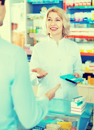 Female pharmacist counseling customer about drugs usage in modern farmacy