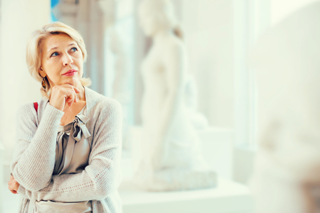 Portrait of positive mature female visitor near sculpture in the historical museum Stockfoto