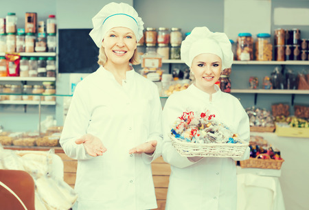 Friendly females staff offering sweets in local confectionery Stock fotó