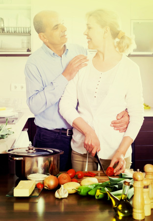 Elderly couple cooking salad at home kitchen Stock Photo