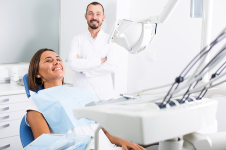 Girl is sitting satisfied in chair after treatment in dental office