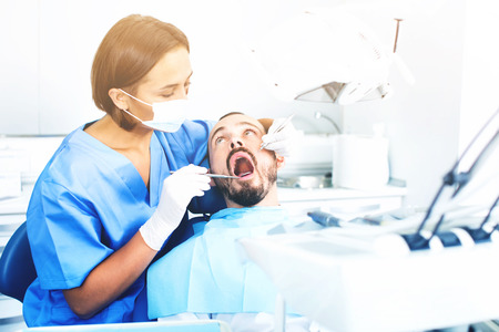 Happy  friendly stomatologist girl in uniform is taking visional inspection of a man on the chair in dental clinic.
