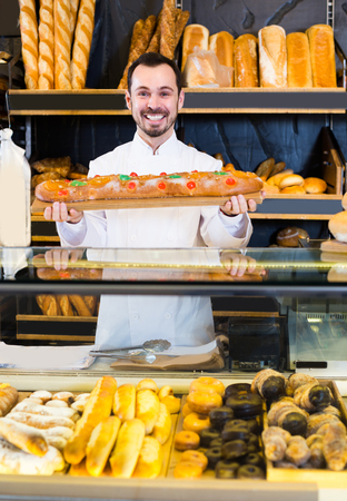 Young male seller is offering fresh festive cake in bakery.