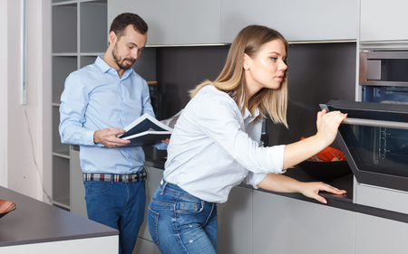 Young loving couple choosing interior for home kitchen in modern studio