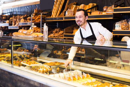 Happy adult male seller offering fresh tasty bun in bakery