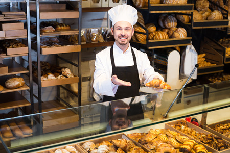 Positive male pastry maker demonstrating croissant in bakery