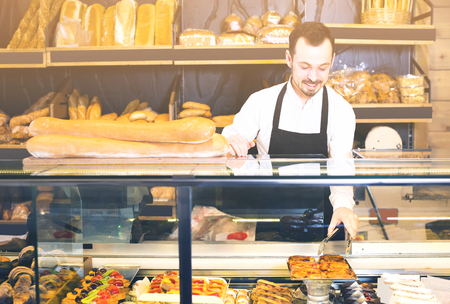 Smiling salesman shows the delicious pastries and cakes at the store