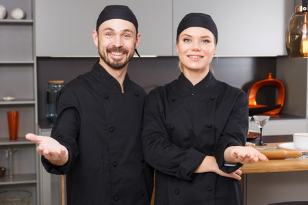 Smiling professional chefs in black uniform standing together in home kitchen Stock fotó