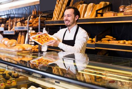 Positive male seller offering fresh tasty bun in bakery