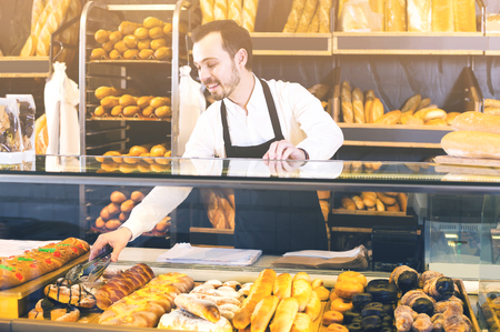 happy male shop assistant demonstrating fresh delicious pastry in bakery