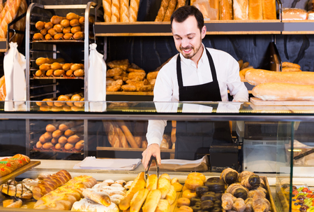 smiling european  male shop assistant demonstrating fresh delicious pastry in bakery