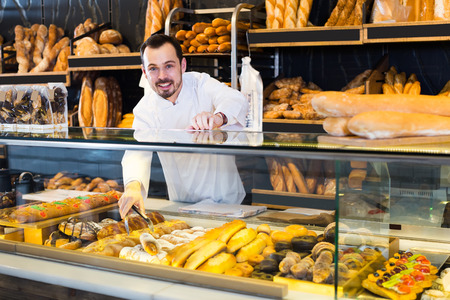 Young baker helps to choose a delicious bread in a shop