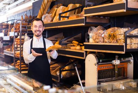 Smiling baker offers white crisp bread in a bakery Imagens