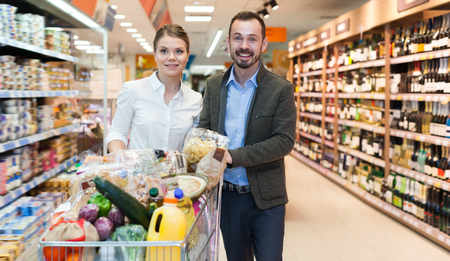 Adult couple is standing with cart with products in the supermarket Stok Fotoğraf