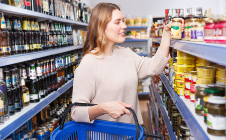 Portrait of woman choosing preserved goods in food store