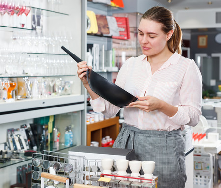 Young  woman buyer choosing new frying pan for kitchen in  store