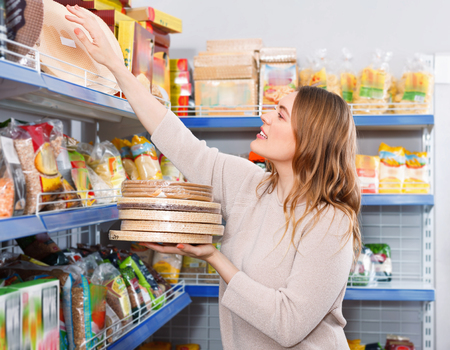 Adult cheerful  woman customer choosing biscuit layers in  grocery food store