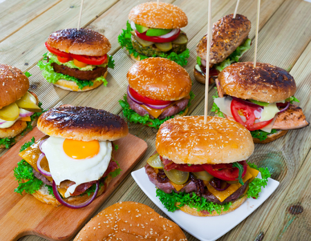 Delicious burgers with rissoles, fish, bacon and vegetables served on plates and cutting boards Zdjęcie Seryjne