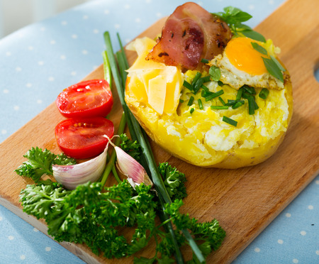 Baked potatoes served with fried egg, bacon and cheese, garnished with fresh scallions