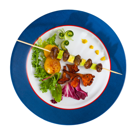 Grilled chicken hearts on skewer with avocado served with roasted chanterelles and vegetables. Isolated over white background