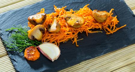 Imagen cercana de pizarra de champiñones recién fritos con zanahoria Foto de archivo