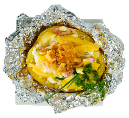 Top view of potatoes baked in foil with stuffing of cheese, bacon and fresh greens