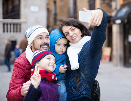 Smiling family of four doing selfie in city at winter day Stock Photo