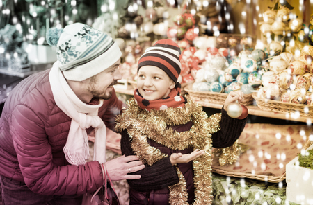 Adult man with small daughter near Christmas decoration Imagens