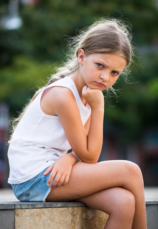 girl in elementary school age looking depressed outdoors in park